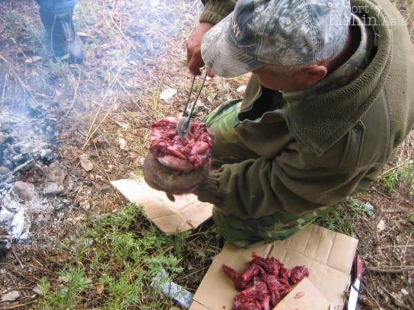 Hot stones being stuffed into the marmot to cook the inside