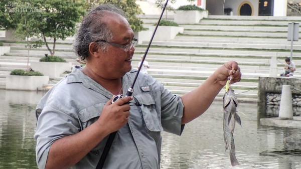 A participant with a tilapia caught on lure.