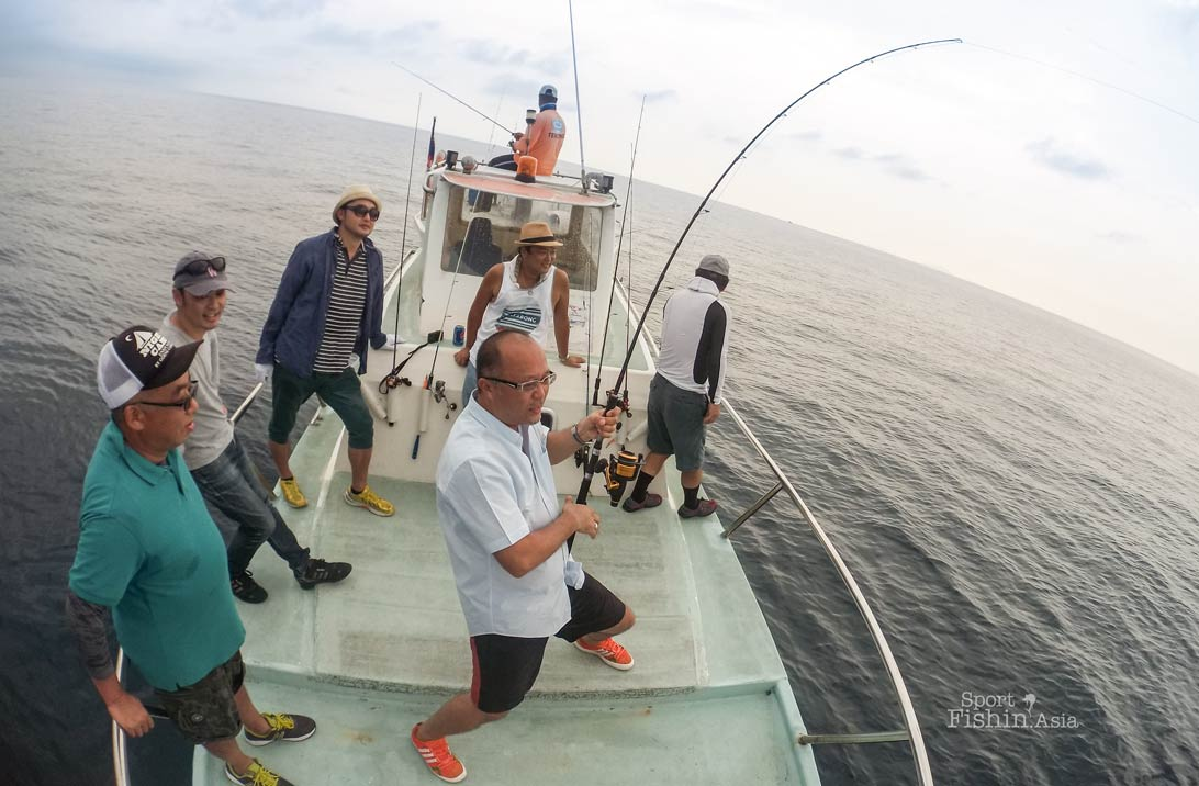 The group of six Japanese friends watching an ongoing battle with a sailfish