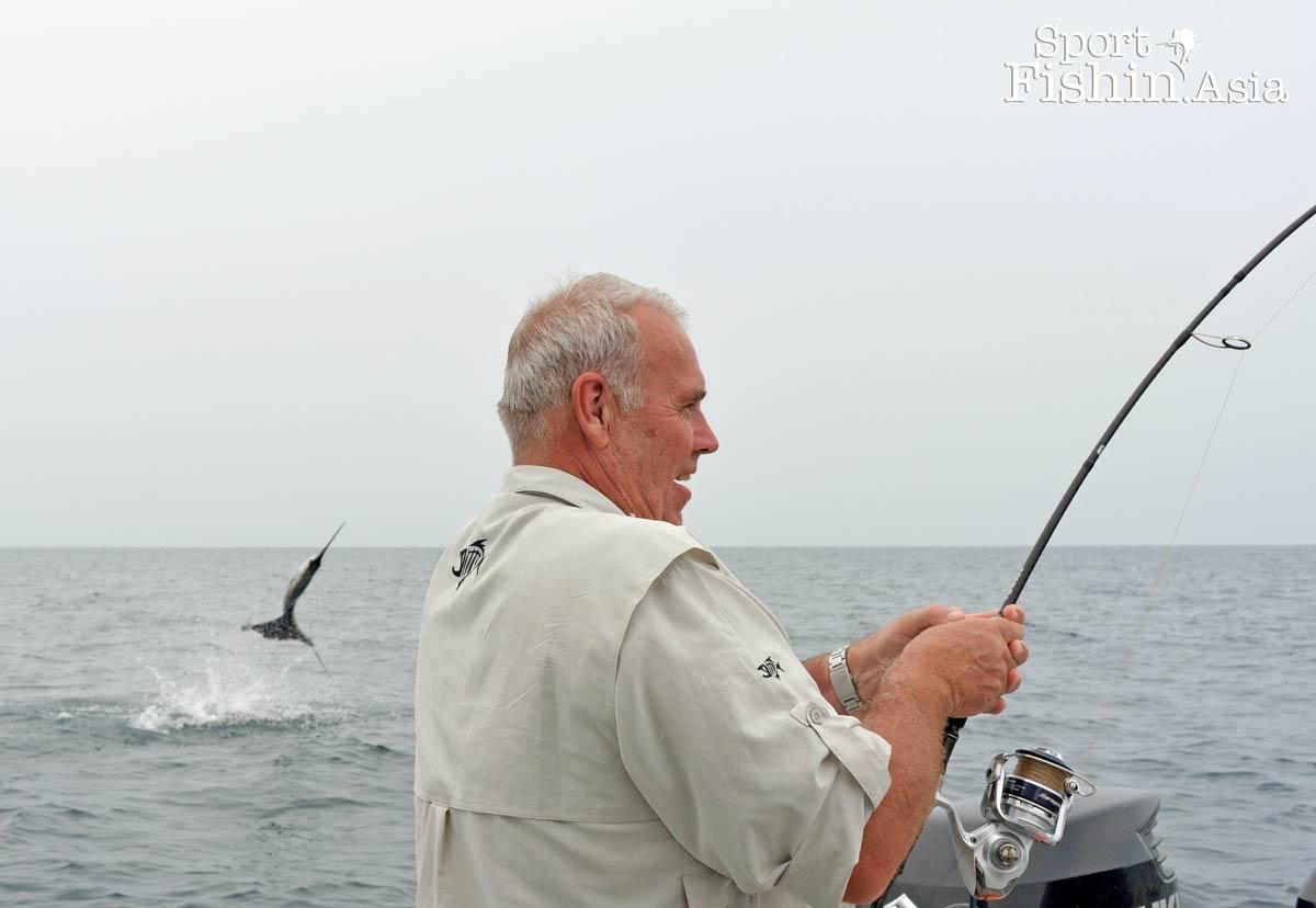 Sailfish jumps into the air behind angler
