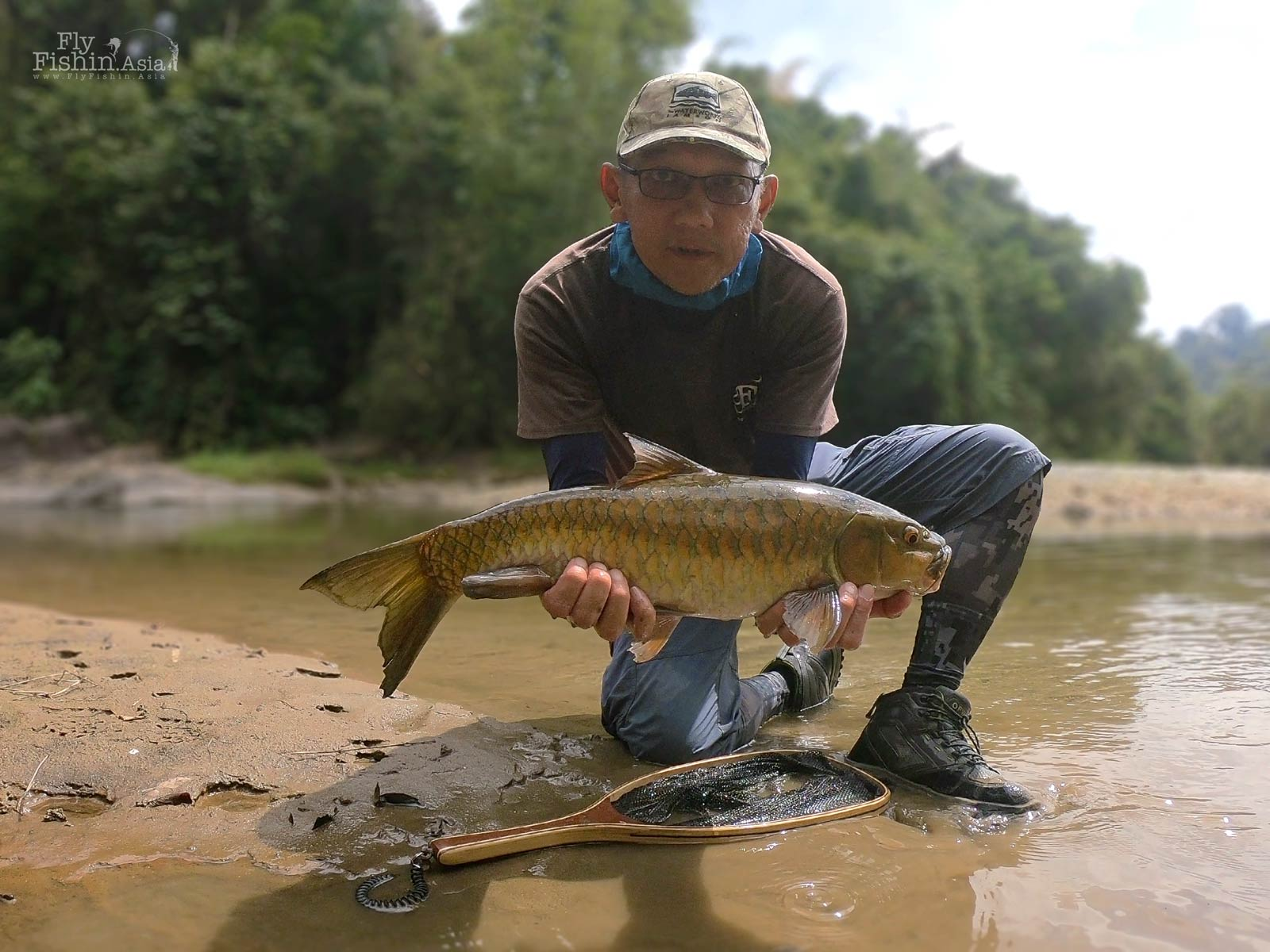 The author wearing the Orvis Ultralight Wading Boots in action holding a Thai Mahseer catch.