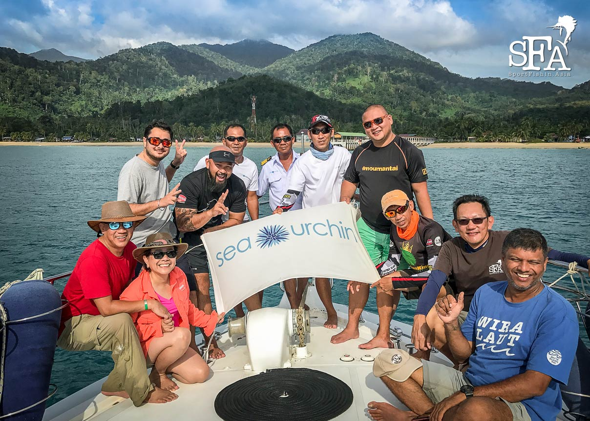Crew and guests of Sea Urchin in front of Tioman island